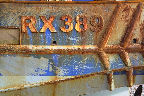 The rusted hull of RX389 fishing boat on Hastings beach photographed by pop artist Trevor Heath